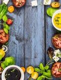 Salade het maken, voedselkader met olie, azijn, tomaten, basilicum en kaas op blauwe rustieke houten achtergrond, hoogste mening Stock Foto