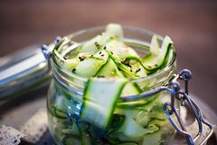 Salade japonaise de concombre avec les graines de sésame noires et blanches dans le pot de maçon avec le couvercle sur le plateau Image libre de droits