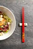 Salade japonaise traditionnelle dans un plat blanc avec des baguettes photos libres de droits