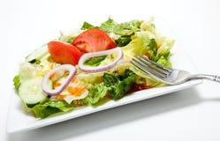 Salade jetée en l'air d'une plaque sur un fond blanc Photographie stock libre de droits