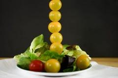Salade lumineuse fraîche d'été d'un plat avec de mini tomates dans une ligne verticale grande Image stock
