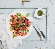 Salade mûre de tomate d'héritage de village avec l'huile d'olive et basilic au-dessus de fond en bois bleu-clair image stock