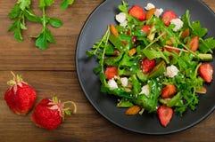 Salade met arugula, aardbeien, kwark, olijfolie, op een zwarte plaat, houten achtergrond Close-up Hoogste mening Royalty-vrije Stock Afbeeldingen