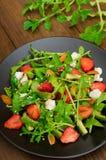 Salade met arugula, aardbeien, kwark, olijfolie, op een zwarte plaat, houten achtergrond Close-up Hoogste mening Stock Afbeelding