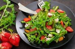Salade met arugula, aardbeien, kwark, olijfolie, op een zwarte plaat, Oude zwarte achtergrond Close-up Hoogste mening Royalty-vrije Stock Afbeelding