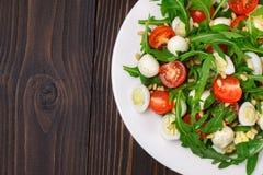 Salade met arugula op een houten achtergrond Stock Afbeeldingen