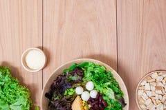 Salade met eieren, kantaloep, broodnoot en groene groente in houten plaat Stock Foto