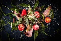Salade met gerookte ham en arugula op de donkere steen hoogste mening Stock Foto