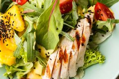 Salade met geroosterde kip, mango, sla, avocado, tomaten, arugula, kaas sause op een witte plaat op houten stock foto