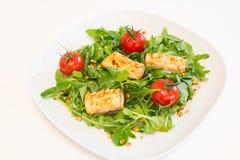 Salade met geroosterde zalm, groene salade en pijnboomnoten op een witte plaat Stock Fotografie