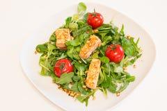 Salade met geroosterde zalm, groene salade en pijnboomnoten op een witte plaat Stock Foto's