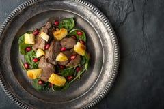 Salade met kippenlever en spinazie op de uitstekende metaalplaat Stock Afbeeldingen