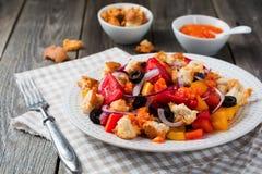 Salade met peper, tomaten, uien, olijven en croutons met sousomna oude houten achtergrond Royalty-vrije Stock Foto