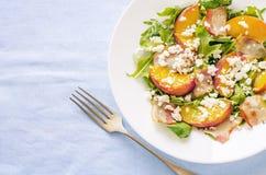Salade met perziken, bacon; arugula, spinazie en geitkaas Stock Afbeelding