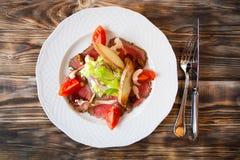 Salade met plakken van gerookte vlees en groenten op een witte plaat Royalty-vrije Stock Afbeelding