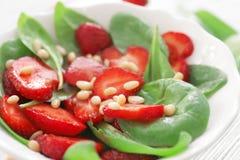 Salade met spinazie, aardbei en pijnboomnoten in plaat Stock Afbeelding
