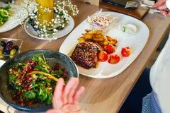 Salade met vlees op een plaat, op een houten lijst Mannelijke handen met een vork en een mes, besnoeiingenvlees stock foto's