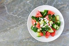 Salade met watermeloen, munt, komkommer en feta, op donkere steen Stock Foto