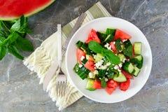 Salade met watermeloen, munt, komkommer en feta, scène over steen Stock Foto's