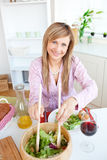 Salade mignonne de portion de femme se reposant dans la cuisine Photographie stock