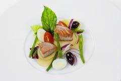 Salade Nicoise avec le thon d'un plat blanc images stock
