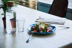 Salade Nicoise sur la table avec la bouteille de l'eau Photo stock