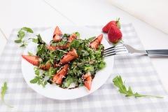 Salade organique saine de r?gime avec l'arugula, les fraises et les amandes dans le plat blanc sur la serviette grise sur un fond photographie stock libre de droits