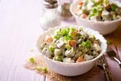Salade russe traditionnelle Olivier dans des cuvettes sur la table en bois images stock