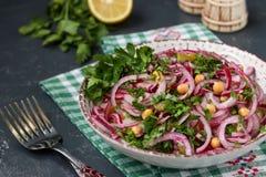 Salade saine avec des pois chiches, des pommes de terre, des oignons rouges et des concombres marinés dans un plat images stock