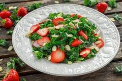 Salade saine de chou frisé avec les fraises et l'amande dans un plat sur la table en bois photographie stock libre de droits