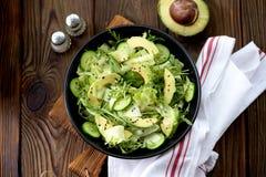 Salade saine organique d'iceberg, d'avocat et de concombre avec l'huile et les graines de sésame d'olive image libre de droits