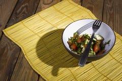 Salade sur un tapis en bambou jaune images stock