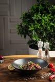 Salade tha?landaise de boeuf dans le plat noir sur le fond en bois image libre de droits