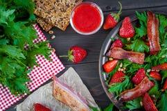 Salade utile de fraise avec l'arugula, les écrous et le lard, sauce à baie Images libres de droits