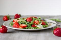 Salade van aardbeien, arugula en kaas op een grijze achtergrond dieet voedsel stock afbeelding