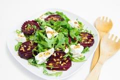 Salade van gebakken biet, eigengemaakte geitkaas, arugula en pijnboomnoten Stock Afbeeldingen