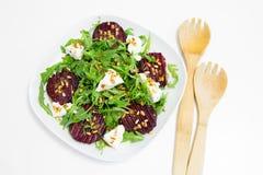 Salade van gebakken biet, eigengemaakte geitkaas, arugula en pijnboomnoten Royalty-vrije Stock Afbeeldingen