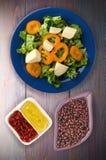 Salade van kaas, sla, graan, peper op een houten achtergrond V Stock Foto's