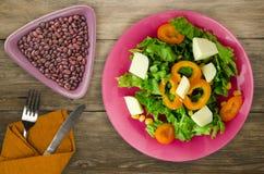 Salade van kaas, sla, graan, peper op een houten achtergrond V Royalty-vrije Stock Afbeeldingen