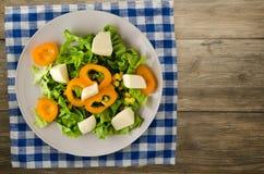 Salade van kaas, sla, graan, peper op een houten achtergrond V Stock Foto