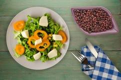 Salade van kaas, sla, graan, peper op een houten achtergrond V Stock Fotografie