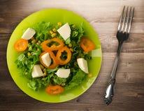 Salade van kaas, sla, graan, peper op een houten achtergrond V Royalty-vrije Stock Fotografie