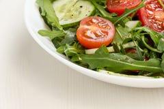 Salade van ruccola, kersentomaten en komkommer royalty-vrije stock foto's