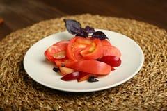Salade van tomaat en rode pruimen met basilicum voor een gezonde voeding stock afbeelding