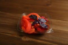 Salade van tomaten en rode pruimen met basilicum in een container royalty-vrije stock afbeeldingen