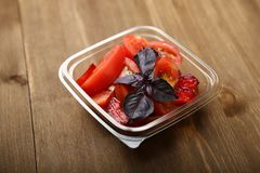 Salade van tomaten en rode pruimen met basilicum in een container stock fotografie