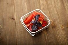 Salade van tomaten en rode pruimen met basilicum in een container stock afbeeldingen