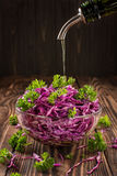 Salade van verse groenten in een saladekom op een houten lijst die met olijfolieclose-up wordt bestrooid stock afbeelding