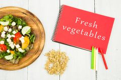 salade van verse groenten en blocnote met tekst & x22; Verse vegetables& x22; stock fotografie