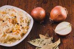 Salade van zuurkool en wortelen met zwarte peper in een witte plaat en een paar uien, laurierbladeren en komijnzaden royalty-vrije stock fotografie